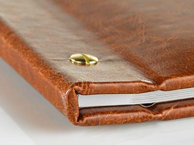 Geschlossenes Pixum Fotobuch mit braunem Ledereinband und Schraubbindung, Detailaufnahme.