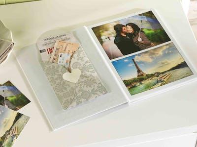 Ein aufgeschlagenes Fotobuch, an dessen Innenseite ein Umschlag für die Aufbewahrung von Reiseandenken geklebt wurde.