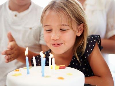 Ein Mädchen feiert ihren Geburtstag und pustet die Kerzen auf ihrer Torte aus.