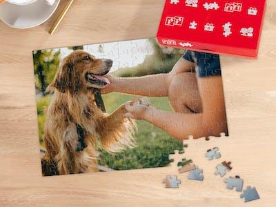 Een tafel met daarop een cappuccino en een Pixum Fotopuzzel met 266 stukjes, bijna helemaal gelegd, met een foto van een hond die met z'n baasje in een park is.