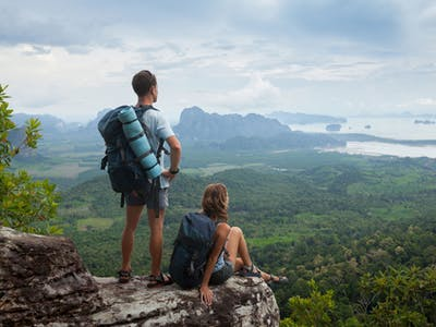 Reisefoto von zwei Backpackern an einem Felsen.