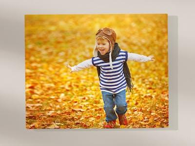 Wandbild mit Foto eines Kindes, das im Laub spielt