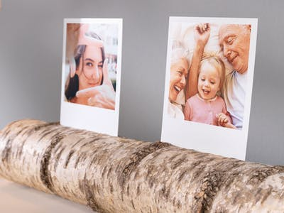 Ein Baumstamm als Fotohalter mit Retro-Prints.