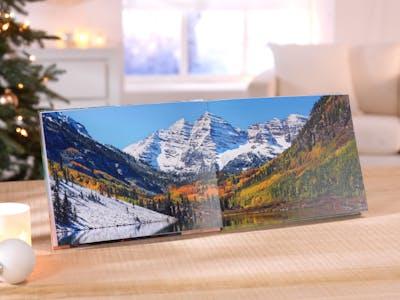 Schneebedecktes Gebirge vor Fluss und Wald.