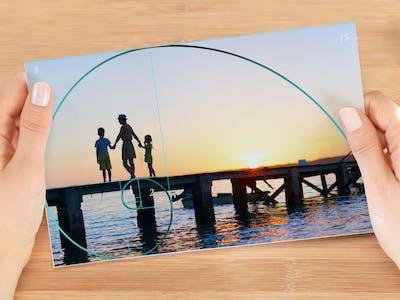 Ein aufgeklapptes Fotobuch, das jeweils ein Foto von einem Berg und einem Segelboot zeigt.
