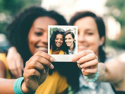 Zwei Freunde halten ein Retro-Foto von Pixum in die Kamera