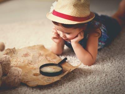Kind sitzt mit einer Lupe vor einer Schatzkarte.