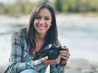 Bild einer jungen Frau, die eine Kamera hält und an einem Fluss sitzt.