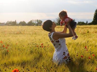 Frau mit Kind im Mohnfeld.