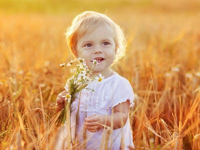 Bild eines Kindes, das mit einer Blume in einem Feld steht.