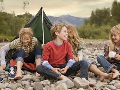 Eine Kindergruppe beim Zelten und Lachen.