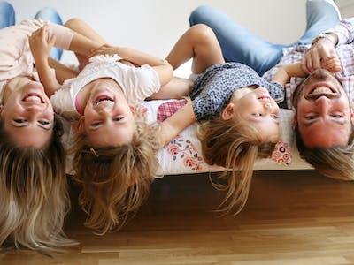 Eine lachende Familie auf dem Bett.
