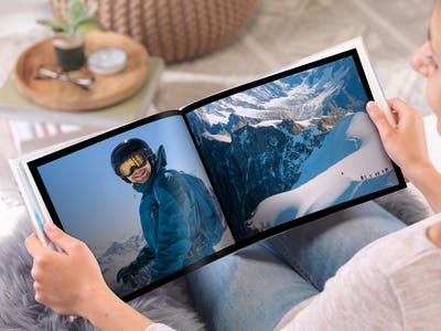 Frau schaut sich ein Pixum Fotobuch an