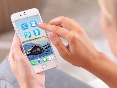 Frau schaut auf Handy und öffnet Pixum Apps.